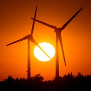 Die Sonne versinkt auf der Ostseeinsel Fehmarn hinter zwei Windrädern, die Menschen sauberen Strom liefern.