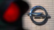 Eine Ampel steht vor dem Firmenlogo des Automobilherstellers Opel in Rüsselsheim auf Rot.