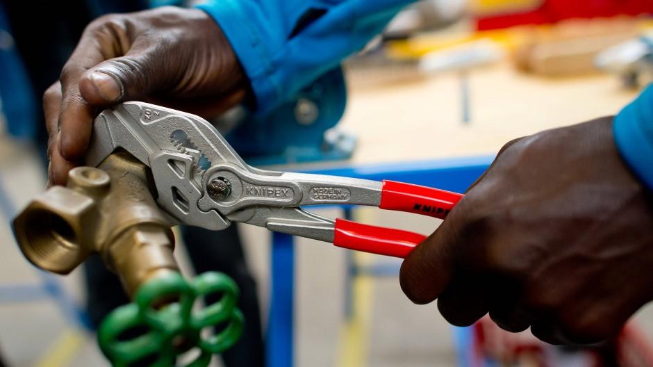 Ein Flüchtling arbeitet in einer Lernwerkstatt an einem Werkstück.