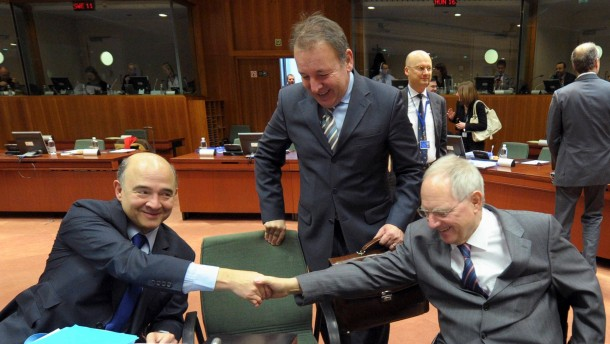 France's Finance Minister Moscovici shakes hands with Germany's Finance Minister Schauble as Slovenian Secretary State Sircelj looks on, during an euro zone finance ministers meeting at the European Union Council in Brussels