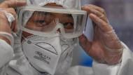 Mitarbeiter der Flughafen-Sicherheit in Schanghai tragen nun auch Schutzkleidung.