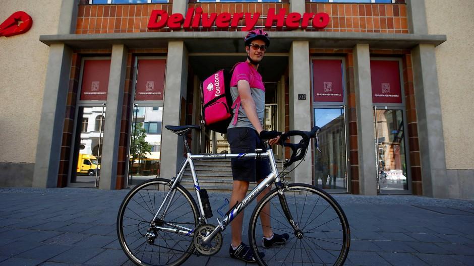 Lang ists her: Ein Fahrer der Delivery-Hero-Marke Foodora steht vor der Unternehmenszentrale in Berlin. Der Konzern hat sein Deutschlandgeschäft inzwischen verkauft.