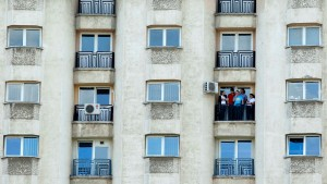 Employees of a private company take a break to smoke on the balcony of a communist-era bloc in downtown Bucharest