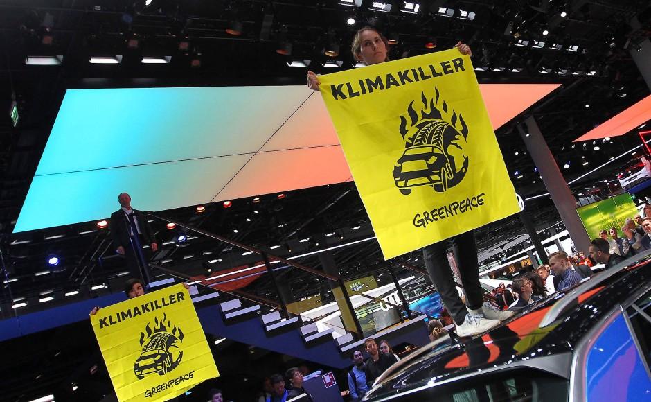 """Während VW-Chef Herbert Diess der Kanzlerin den VW-Stand zeigte, stiegen mehrere junge Leute auf Auto-Dächer und entfalteten gelbe Transparente der Umweltorgansiation Greenpeace: : """"Frau Merkel, glauben Sie nicht den Lügen der Autoindustrie"""", rief eine junge Frau."""