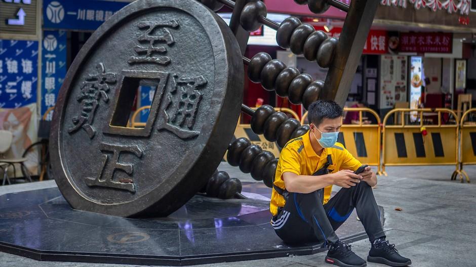 Tradition trifft Moderne: Smartphone-Nutzer vor einer Skulptur mit übergroßer historischer Münze und analogem Rechengerät in der Stadt Guangzhou