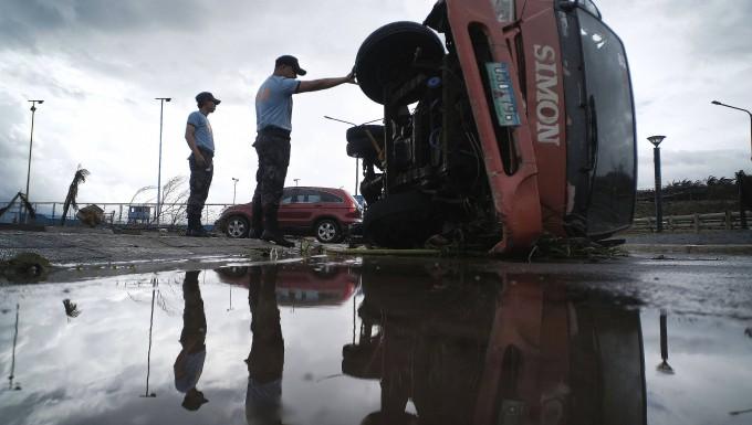 """Auf den Philippinen inspiziert die Polizei einen Lastwagen, der von Windböen des Taifuns """"Kammuri"""" umgestoßen wurde."""