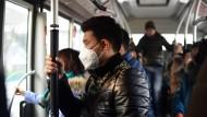 Nicht ohne meine Maske: In asiatischen Metropolen gehört Atemschutz zum Arbeitsweg dazu.