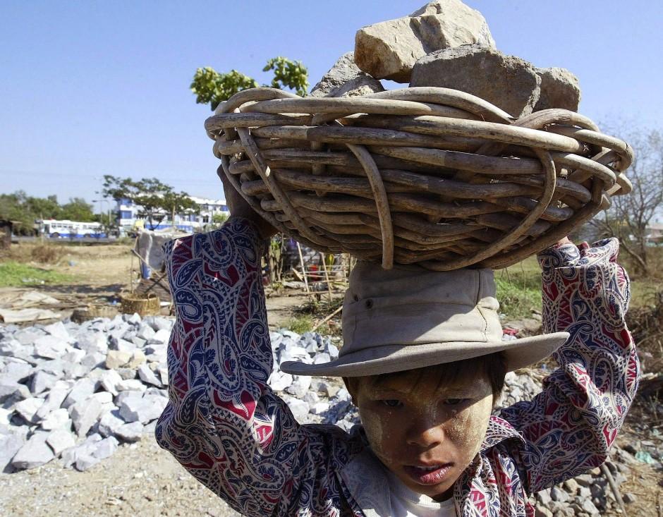 Ein 13-jähriger Junge trägt in Myanmar bei Straßenbauarbeiten einen Korb mit Steinen auf seinem Kopf.