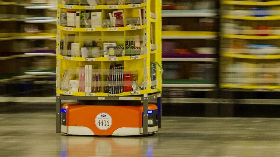 In einem amerikanischen Amazon-Versandzentrum transportiert ein orangefarbener Roboter ein Regal mit Büchern und Geschenken direkt zur Verladestation.