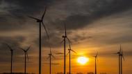 """Die Sonne leuchtet beim Sonnenaufgang zwischen Wolken über dem Windpark """"Odervorland"""" im Landkreis Oder-Spree."""