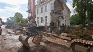 Ein Bagger steht vor einem durch die Flut beschädigten Haus in Bad Neuenahr.