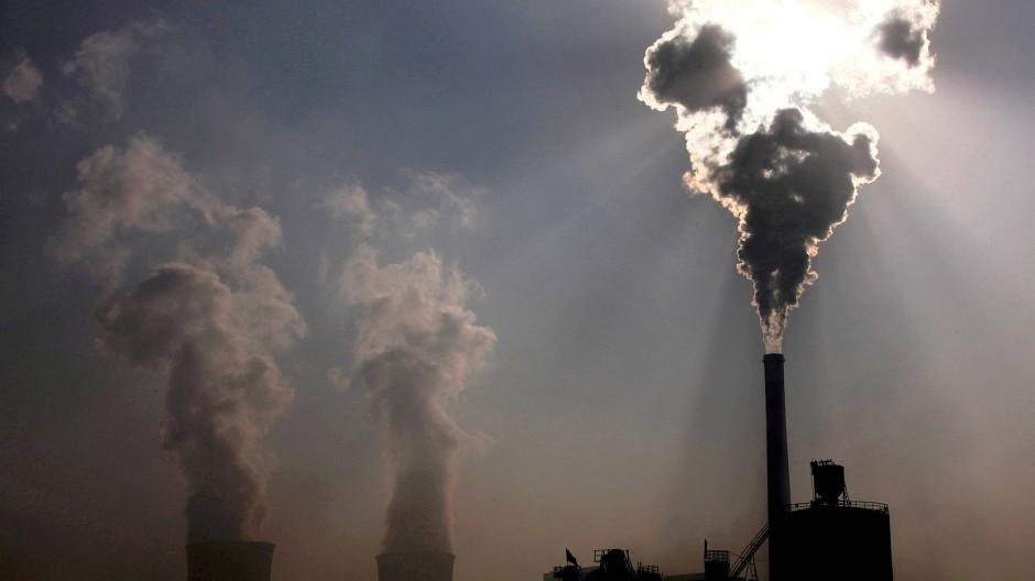 Wasserdampf steigt aus den Kühltürmen eines Kohlekraftwerks in Baotou, China.