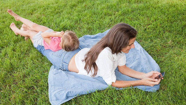 Mother and daughter lying on grass