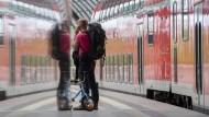 Die Reiseplanung bleibt schwierig: Ein Mann telefoniert am Berliner Hauptbahnhof vor einem Regionalzug der Deutschen Bahn.