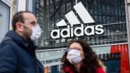 Zwei Menschen stehen mit Schutzmasken vor einer Adidas-Filiale in Berlin.