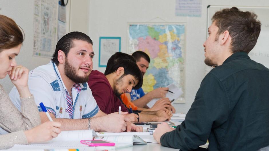 Männliche und weibliche Flüchtlinge lernen zusammen Deutsch.