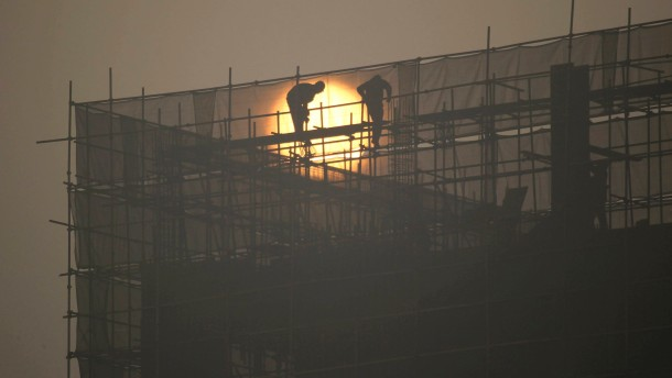 Labourers install scaffolding at a residential building construction site during sunrise on a hazy day in Zhengzhou