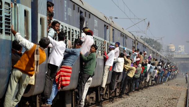 Commuters hang onto a crowded local passenger train in the eastern Indian city of Patna