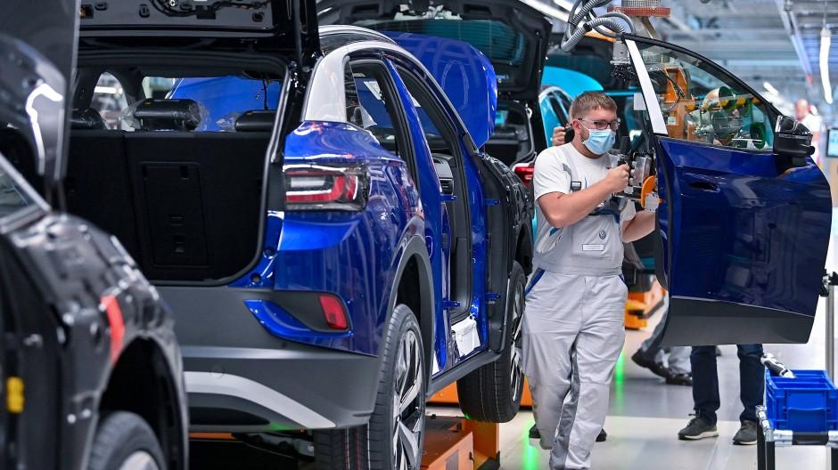 Ein Mitarbeiter im Volkswagenwerk in Zwickau komplettiert einen VW ID.4