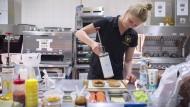 Lasst uns zwei Burger bauen: Pölkings Kollegin Lisa Kleemann bringt in der Versuchsküche von McDonald's die Sauce auf die Brötchen.