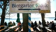 Besucher eines Biergartens am Ammersee genießen das schöne Wetter.