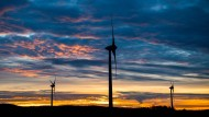 Die aufgehende Sonne verfärbt den Himmel hinter Windrädern in der Region Hannover.