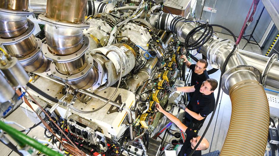 Ein Techniker und zwei Ingenieure arbeiten in einem MTU-Prüfstand an einem mobilen MTU-Gasmotor von Rolls-Royce.