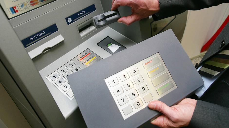 """Ein Mitarbeiter der Sparkasse Koblenz demonstriert """"Skimming"""" an einem Geldautomaten: Kriminelle montieren Vorsatzgeräte (oben) an den Kartenschlitz des Geldautomaten, um die Kartendaten auszulesen. Mittels einer aufgesetzten Zusatztastatur (unten) oder einer Mini-Kamera gelangen sie außerdem an die PIN-Nummer der Karte."""