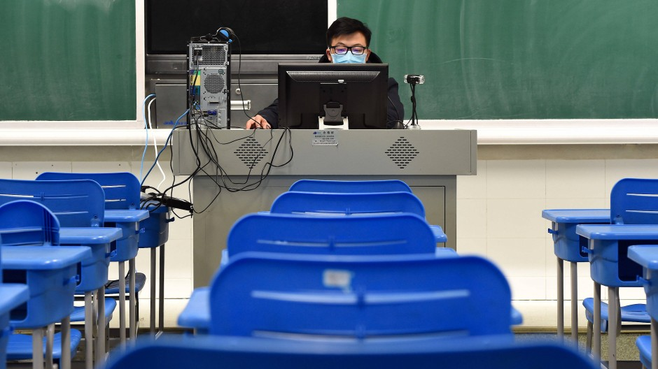 Cyberunterricht in China: Ein Geschichtslehrer sitzt in einem leeren Klassenzimmer vor einem Computer.