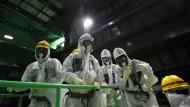 Medienvertreter in Schutzanzügen besichtigen den Reaktor 4 des Atomkraftwerks Fukushima