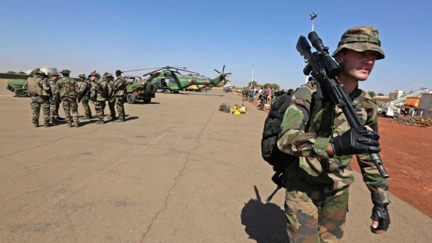 A French sniper carries his weapon at the Mali air force base near Bamako