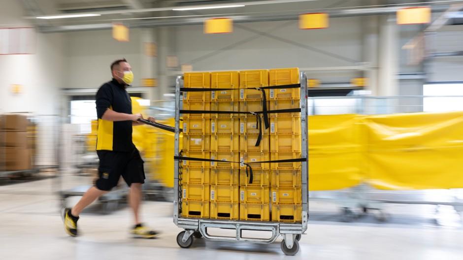 Vor dem Transport zum Endkunden: Ein Mitarbeiter der DHL schiebt einen Behälterwagen durch einen Zustellstützpunkt in Sachsen.