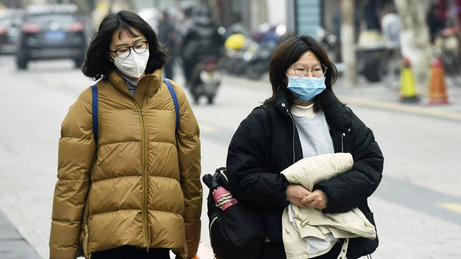 In Hangzhou laufen Passanten mit Gesichtsmasken über die Straße.