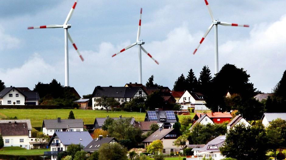 Windräder des Windparks Schöneseiffen drehen sich hinter Wohnhäusern.