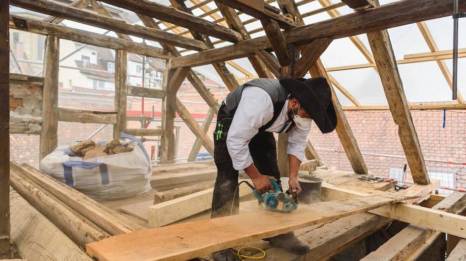 Ein Zimmermannsgeselle arbeitet bei der Sanierung des Baudenkmals Riegelhof in Bamberg.