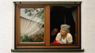 Eine Rentnerin blickt aus dem Fenster.
