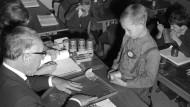 Damals wurde das Sparen noch gelehrt: Ein Bankmitarbeiter zeigt Schulkindern im Jahr 1965, wie sie Geld zählen.