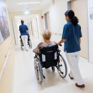 Zwei Pflegerinnen schieben in einem Klinikum Patienten mit Rollstühlen durch einen Flur.