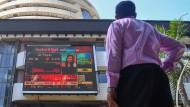 Ein Mann steht vor der Kurstafel in Indien: Der Aktienmarkt dort erlebte den schlimmsten Handelstag aller Zeiten.