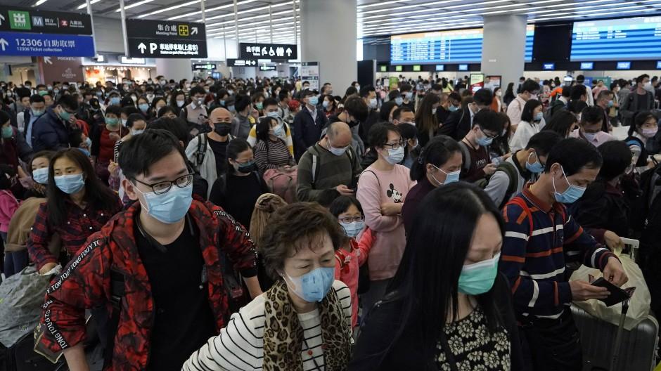 Fahrgäste tragen Atemschutzmasken in der Abfahrtshalle eines Bahnhofs für Hochgeschwindigkeitszüge.