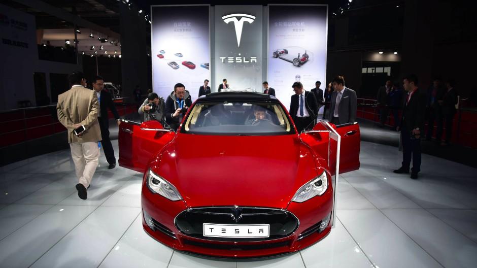 Objekt der Begierde: In Shanghai begutachten Besucher der Auto-Messe ein Tesla-Modell.