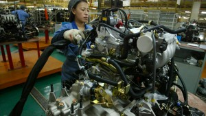 File photo of a Chinese worker assembling the engine of a Hafei vehicle at the production line of Hafei Motor Co Ltd, in Harbin