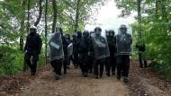 Die Idylle Hambacher Forst trügt: Polizisten bringen sich am Donnerstag im Hambacher Forst in Stellung, um die Räumung der Umweltaktivisten-Camps zu vollziehen.