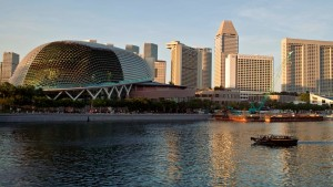 A tourist boat sails up the Singapore river as it passes in front of the skyscrapers of Marina Bay
