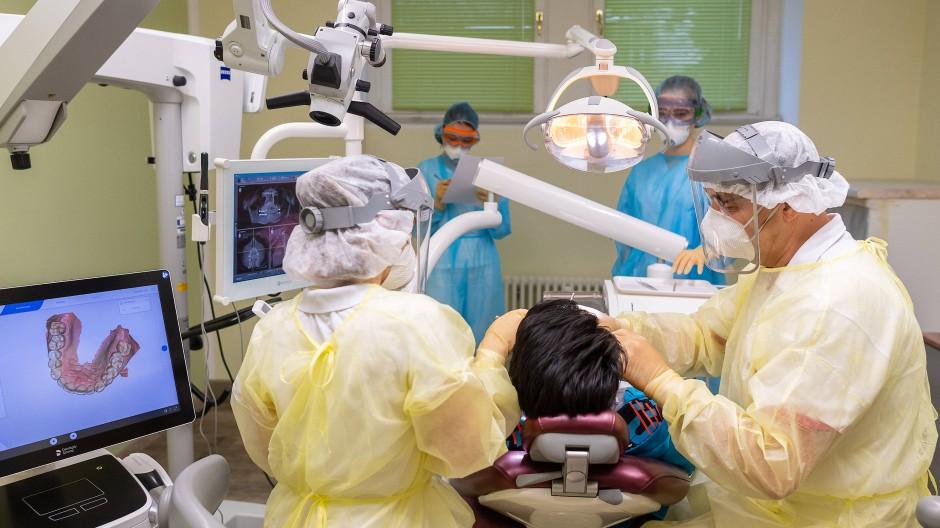 Immer mit Schutzausrüstung: Ein Zahnarzt in Dresden behandelt einen Corona-Patienten.