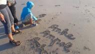 Im Sand statt auf Papier: Antonia Roser übt Schreibschrift.