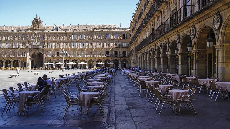 Nur wenige Menschen sitzen auf der Terrasse eines Restaurants auf der Plaza Mayor in Salamanca.