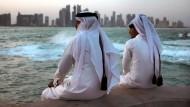 Zwei junge Qataris blicken auf die Skyline Dohas.