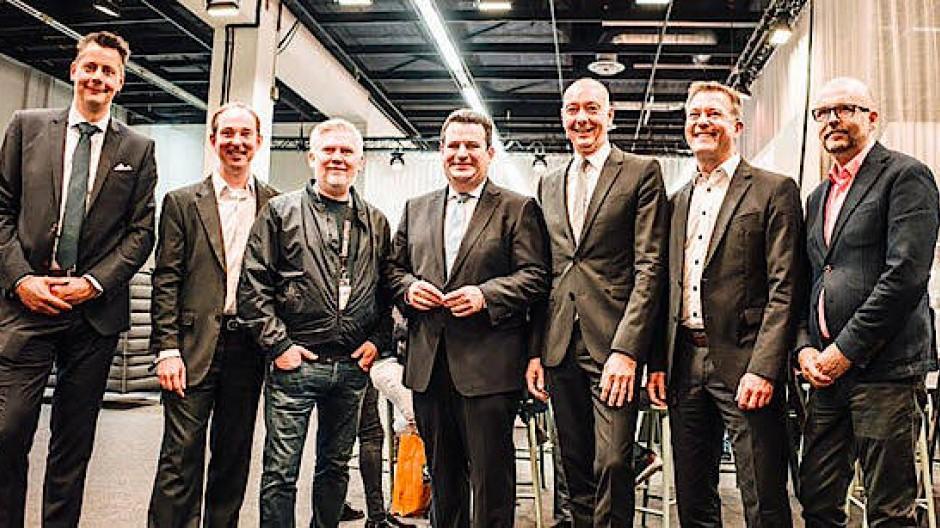 Bild des Anstoßes: Bundesarbeitsminister Hubertus Heil (SPD) inmitten sechs mittelalter Männer in dunklen Jacketts.