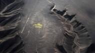 Greenpeace-Aktivisten stehen auf ihrem Schriftzug neben dem Geoglyphen in Nazca